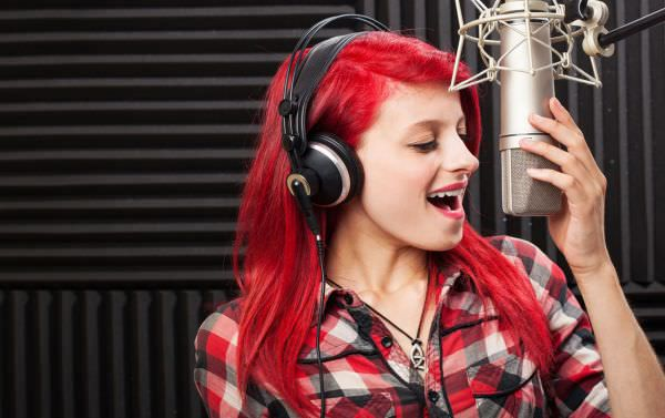 Recording artist singing into a microphone in a sound studio.
