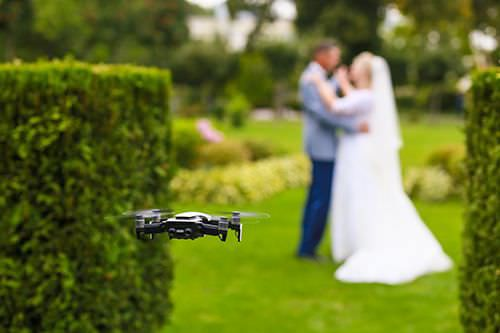 Flying drone taking photo of couple on wedding day.