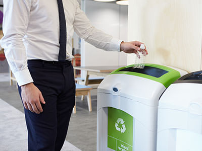 Man in office throwing bottle in recycling bin.